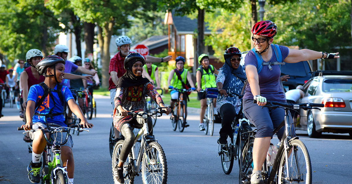 Adults and kids smiling and biking together on a Slow Roll bike ride in Saint Paul