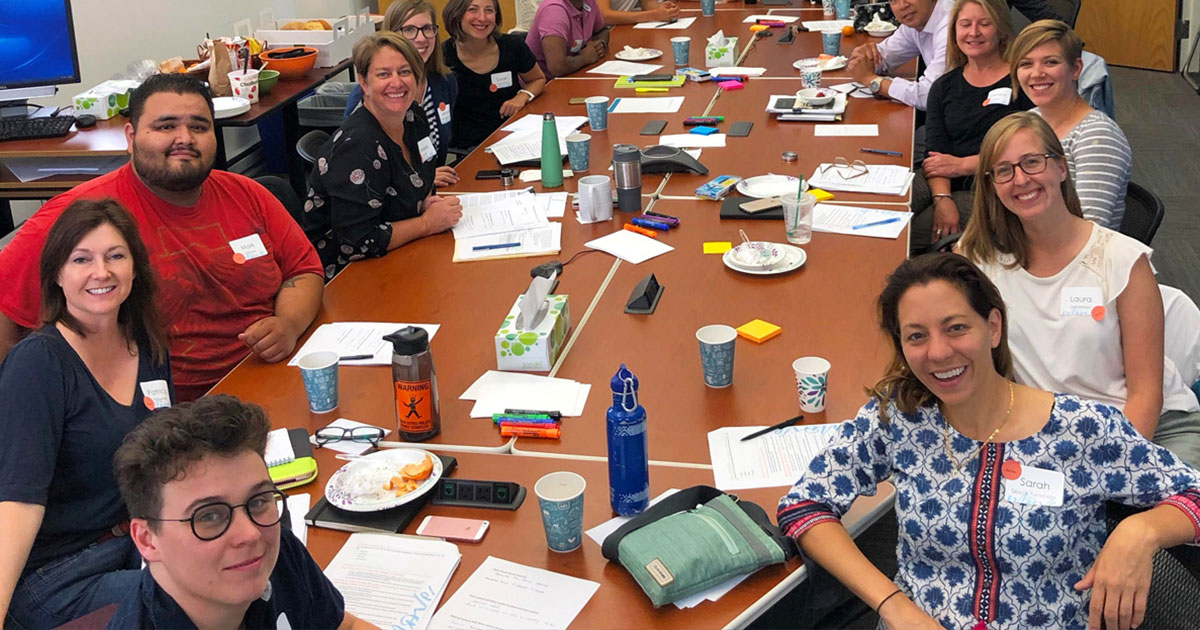 Move Minnesota board and staff smile together around a large conference table during a group retreat.