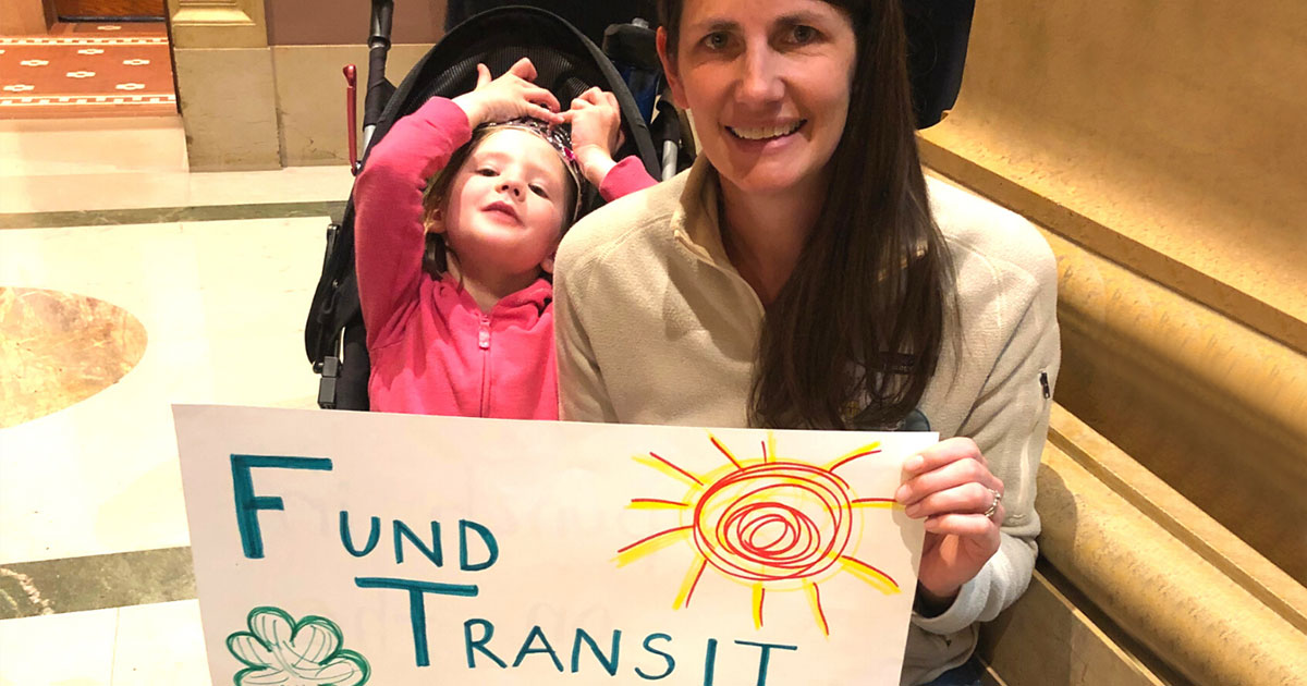"Person smiling with child in stroller, holding a sign that reads ""Fund Transit"""