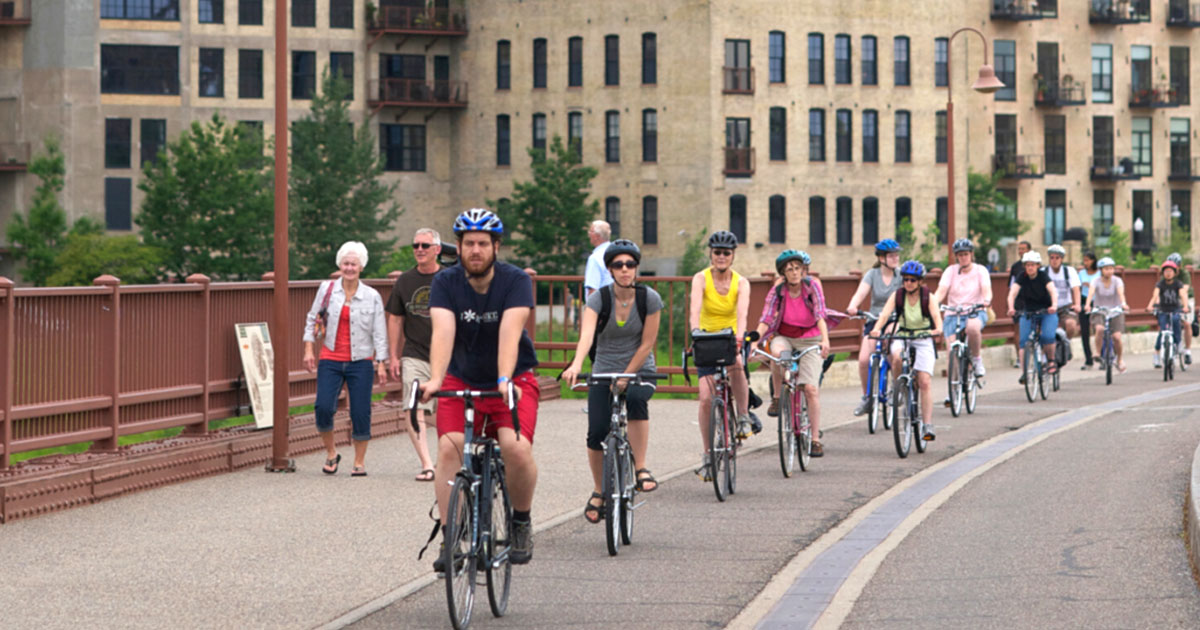 A group of bike riders riding along the Stone Arch Bridge.