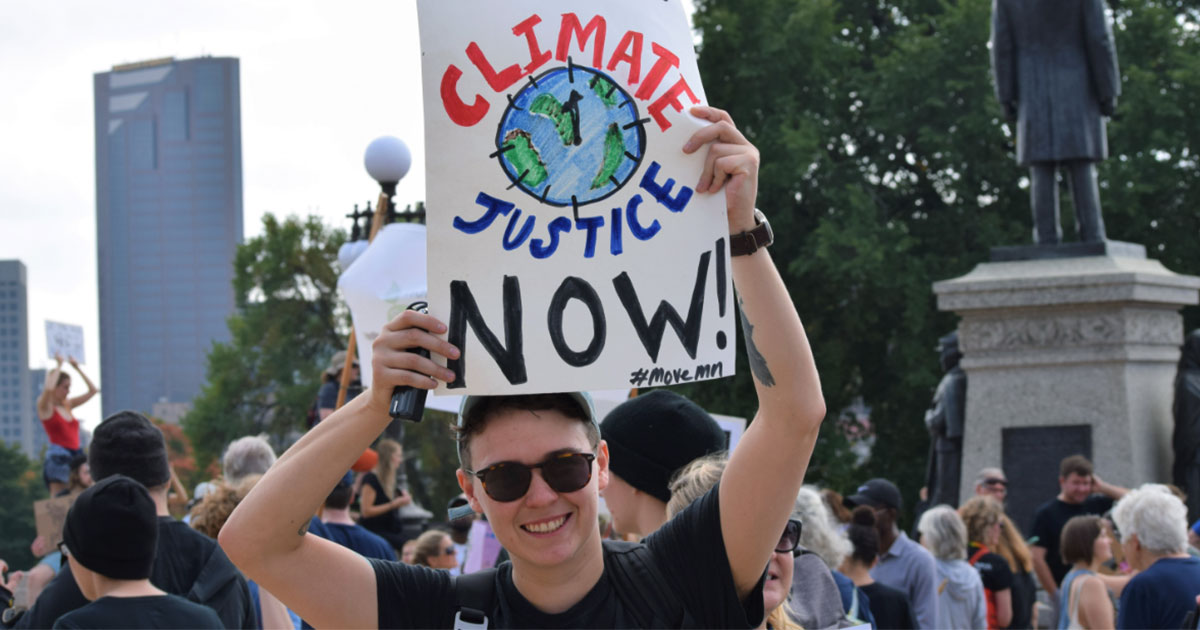 "Move Minnesota staff, Finn McGarrity, holding sign ""We want climate justice now!"" at Youth Climate Strike"