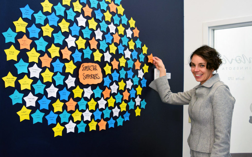 Move Minnesota Executive Director, Jessica Treat, placing a paper star with a donor's name onto a wall full of stars for the board alumni challenge