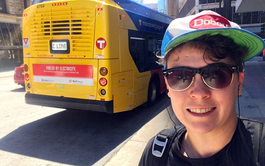 "Move Minnesota community organizer Finn McGarrity takes a selfie next to a new C Line bus that says ""Fueled by Electricity"" on the back."