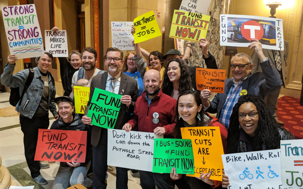 Transit advocates smile for a group photo at the MN State Capitol holding colorful signs with messages demanding investment in transit, bicycling, and walking.