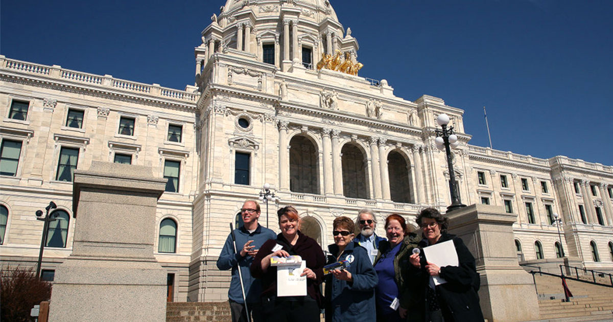 Transit advocates smiling and posing in front of the State Capitol