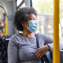 Woman wearing a face mask on the bus