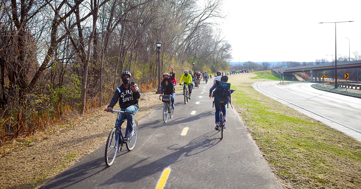 Many people biking on Saint Paul's new Ayd Mill Trail on opening day. The photo also shows the trail is fully separated from the road next to it.