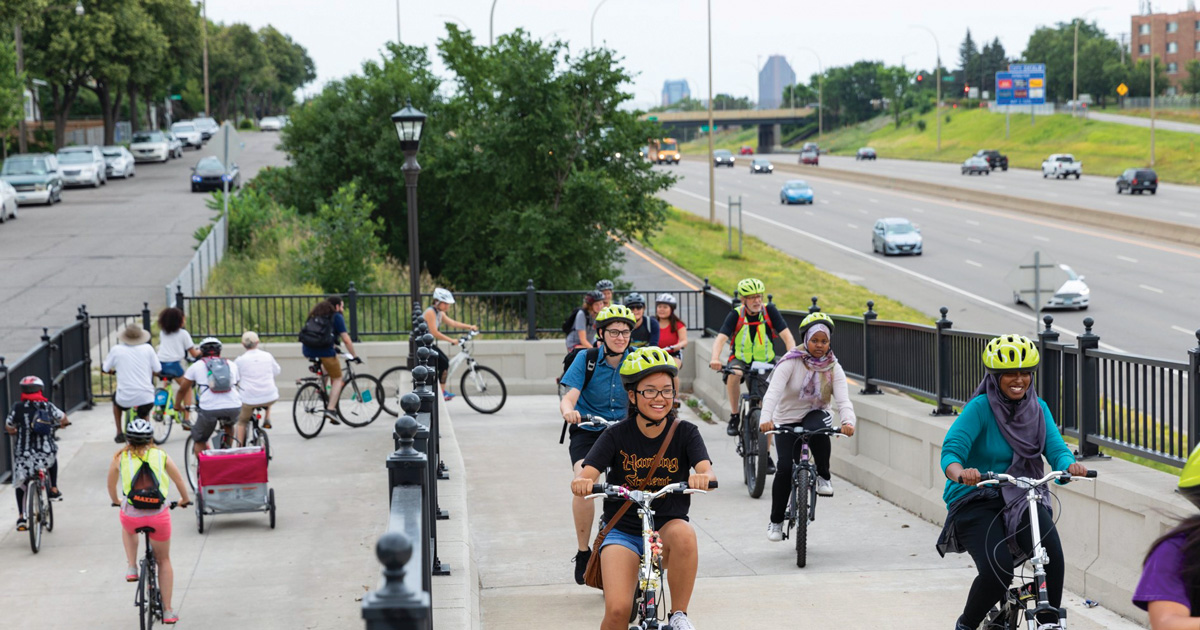 A group youth riding their bikes on a a bridge parallel to I-94 in Saint Paul