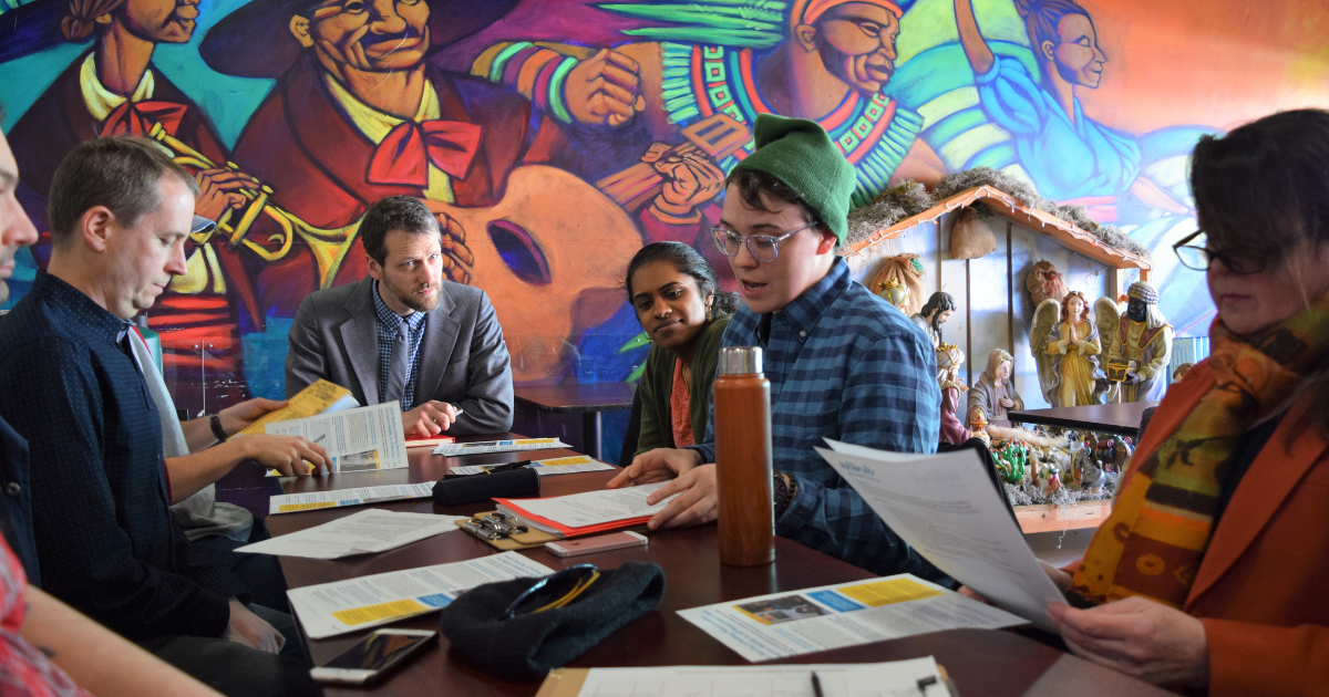 Finn McGarrity, Move Minnesota Community Organizer speaking to a roundtable of attendees at a Minneapolis in-district meeting