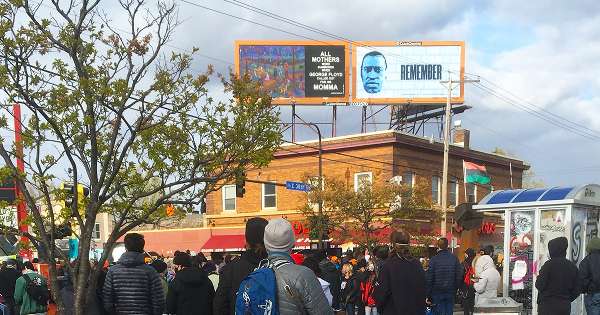 A crowd gathered at George Floyd Square in Minneapolis with billboard messages dedicated to George.