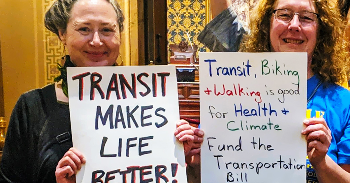"""Advocates hold signs with pro-transit messages. One sign says, """"Transit Makes Life Better."""""""
