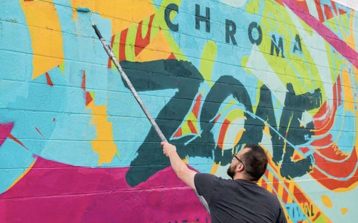 An artist paints a colorful Chroma Zone mural for the festival in Saint Paul.
