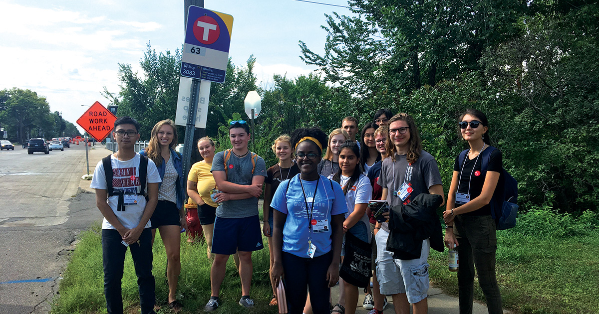 A group of students at a Metro Transit bus stop.